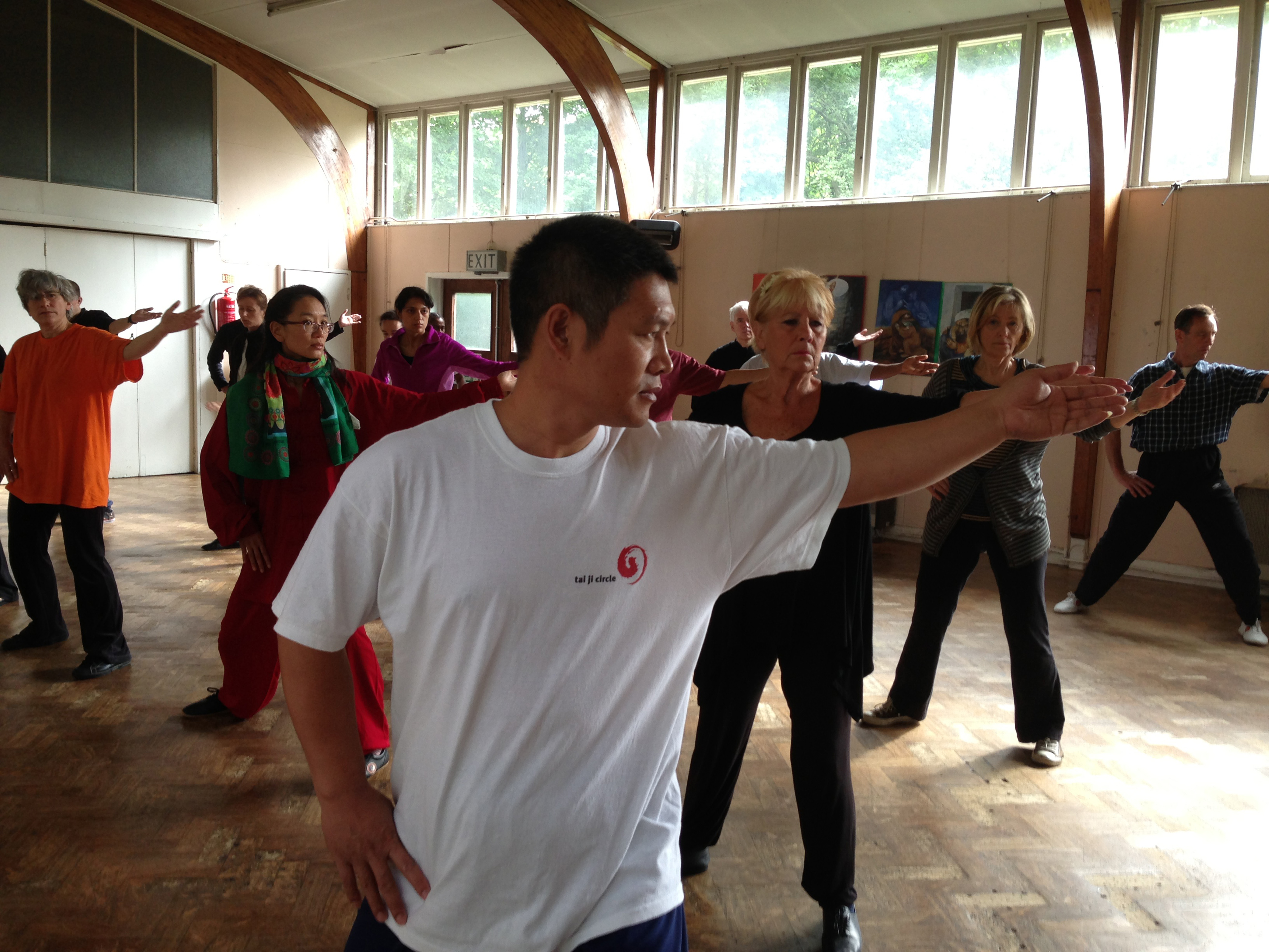 Teaching taiji to a group of students in a hall
