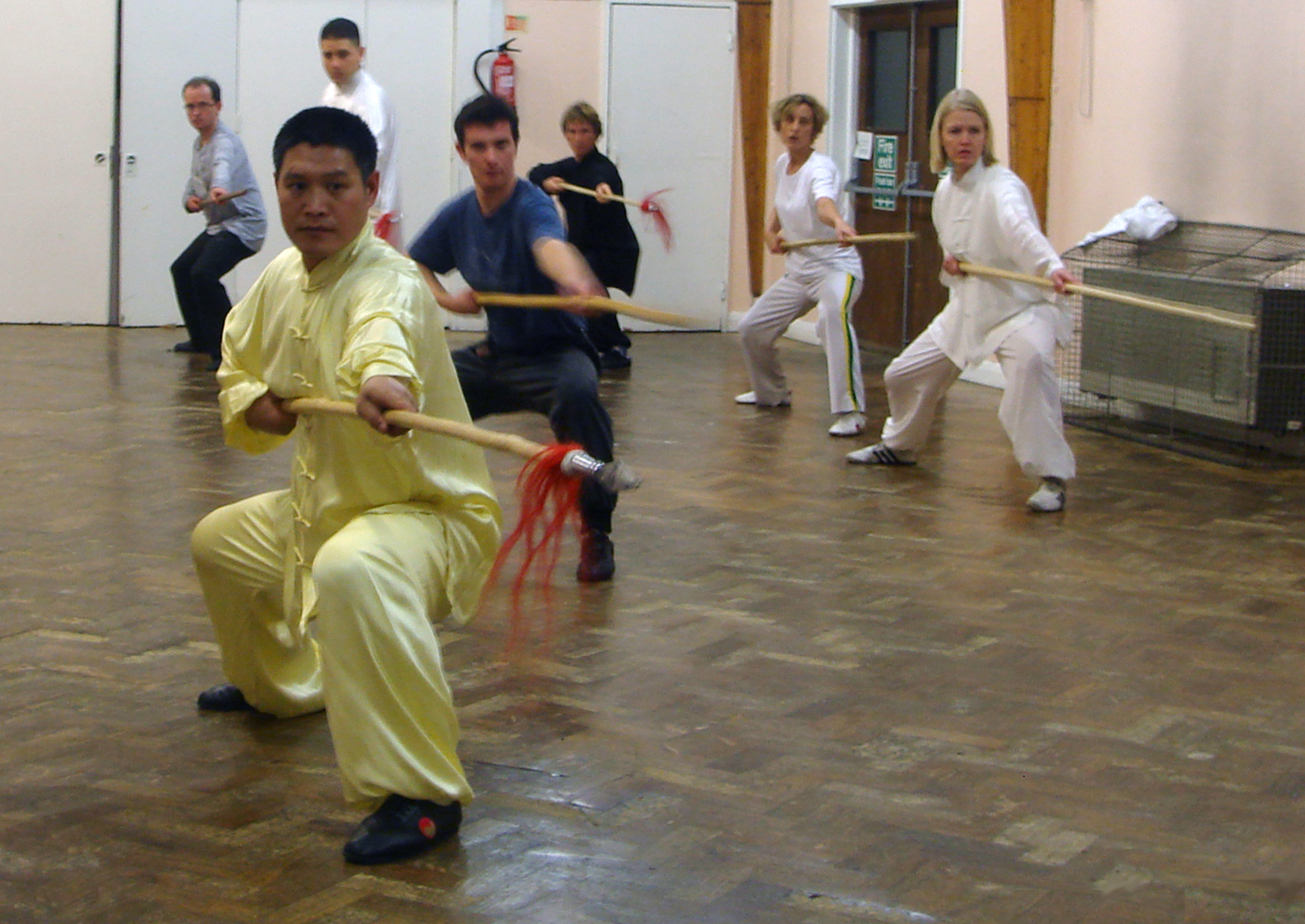 Teaching spear form to a group of students in a hall